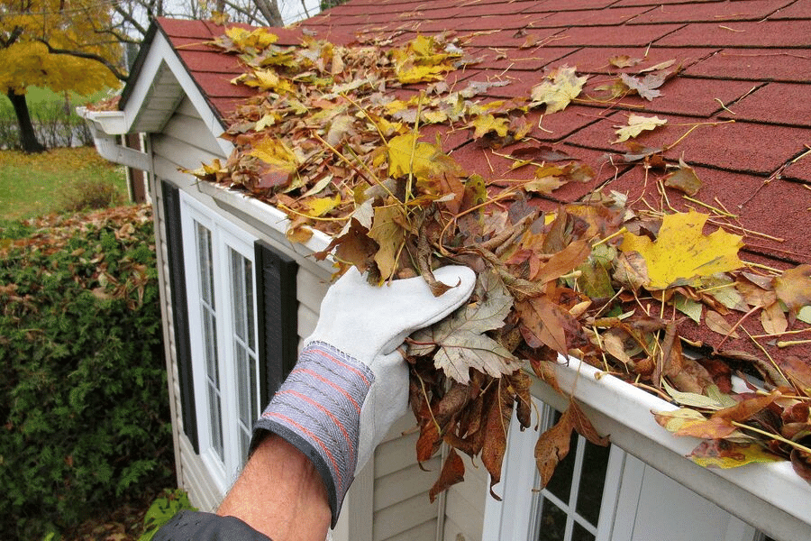 A Logan handyman removing leave from the gutter of a house.