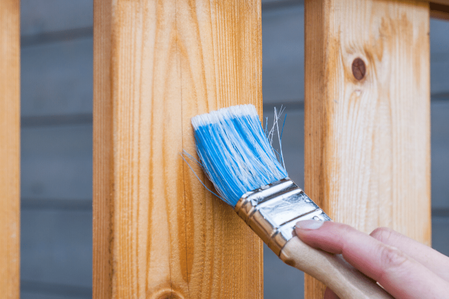A handyman staining a fence in Cache Valley with a blue brush.