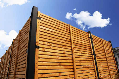 The corner of a wooden fence with a blue sky in the background.